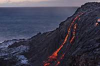 A couple on the right sets up to take evening photographs of the lava flowing down a large cliff towards the ocean, Hawai'i Volcanoes National Park, Hawai'i Island.