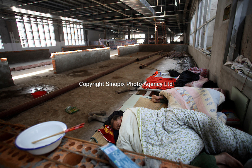 Workers sleep in the newly being constructed larger factory at Amity Printing Co in Nanjing,  which is a joint venture with the United Bible Society that produces millions of bibles annually..03 Nov 2007