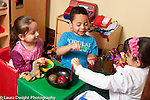 Preschool3-4 year ols two girls and a boy in pretend play area in dressup clothes sitting together and talking