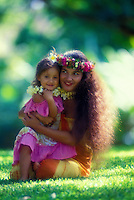 A beautiful Polynesian woman and her daughter, both dressed in colorful aloha wear with plumeria and haku leis, sit embracing on the grass.