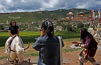 Tourists pay to be photographed with a Yak and a Tibetan in front of the Ge Ban Song Temple in Da Qing county. Da Qing is a Tibetan area and part of the Tibetan Plateau and has been designated by the Chinese authorities as Shangrila. It is being developed as a tourist mecca with a new airport and hotels catering for thousands of tourists..14 Jul 2005
