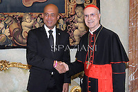Cardinal Tarcisio Bertone receives  President of Haiti Michel Martellyat the end of a private audience in his private library at the Vatican on November 22, 2012
