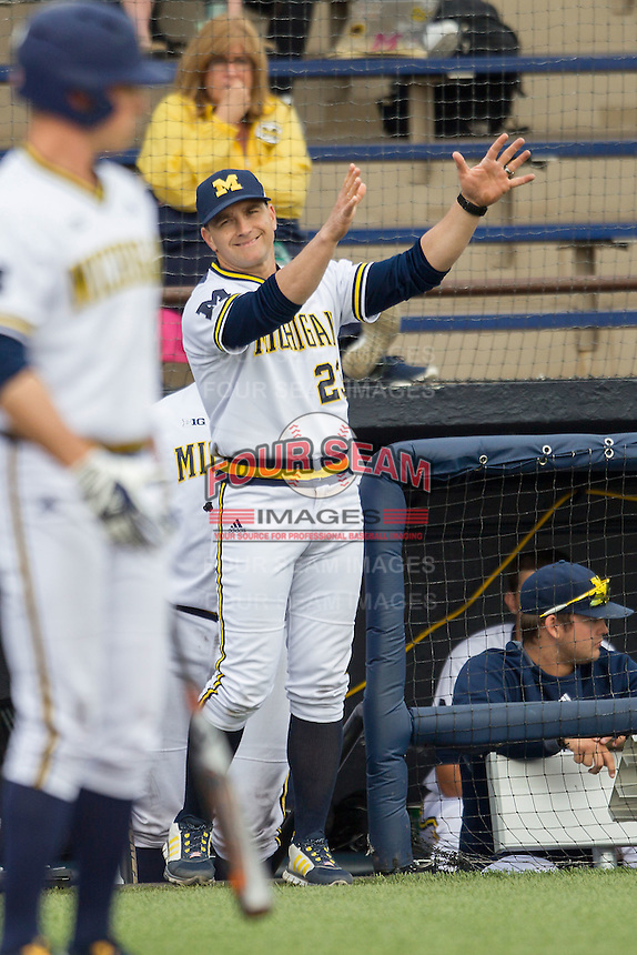 Michigan Wolverines Head Coach Erik Bakich (23) flashes a sign to the batter during the game against the Toledo Rockets on April 20, 2016 at Ray Fisher Stadium in Ann Arbor, Michigan. Michigan defeated Bowling Green 2-1. (Andrew Woolley/Four Seam Images)