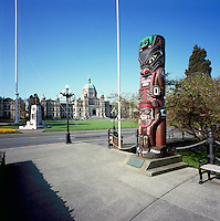 Victoria, BC, Vancouver Island, British Columbia, Canada - Kwakwaka'wakw (Kwakiutl) Totem Pole (carver Henry Hunt) at Inner Harbour, BC Parliament Buildings and Cenotaph War Memorial in background