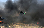 Palestinian women hurl stones towards Israeli security forces during clashes in tents protest where Palestinians demanding the right to return to their homeland, at the Israel-Gaza border, in Khan Younis in the southern Gaza Strip, on May 11, 2018. Photo by Ashraf Amra