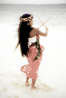 Young woman dancing hula on the beach with puili ( slit bamboo ) instrument