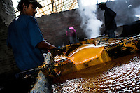 A Colombian peasant mixes a hot mass of sugar cane juice during the processing of panela in a rural sugar cane mill (trapiche) in Santa Ana, Valle del Cauca, Colombia, 30 May 2012. Panela, a solid block of raw, unrefined sugar, is made by cooking and evaporation of the sugar cane juice into a golden, sticky syrup which is then poured into the wooden molds and allowed to solidify. Having the taste like a cross between molasses and brown sugar, panela is served as a hot or cold infusion (aguapanela). Due to the large amounts of proteins, vitamins and minerals, panela is believed to have healing powers. Cheaper than sugar, it is consumed by the majority of Colombians and it is a major source of calories for children from families with low socioeconomic status. With more than 70,000 farms that cultivate sugarcane for mills, panela production is an important economic activity in the Colombian countryside, employing around 350,000 people and being the second largest source of jobs after agricultural coffee production.