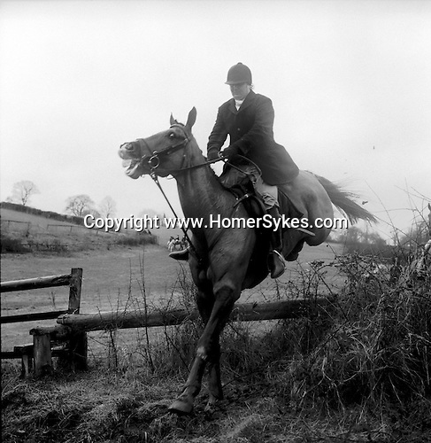The Duke of Beauforts Hunt...A mounted follower takes a jump in pouring rain. Near Luckington, Gloucestershire...Hunting with Hounds / Mansion Editions (isbn 0-9542233-1-4) copyright Homer Sykes. +44 (0) 20-8542-7083. < www.mansioneditions.com >..