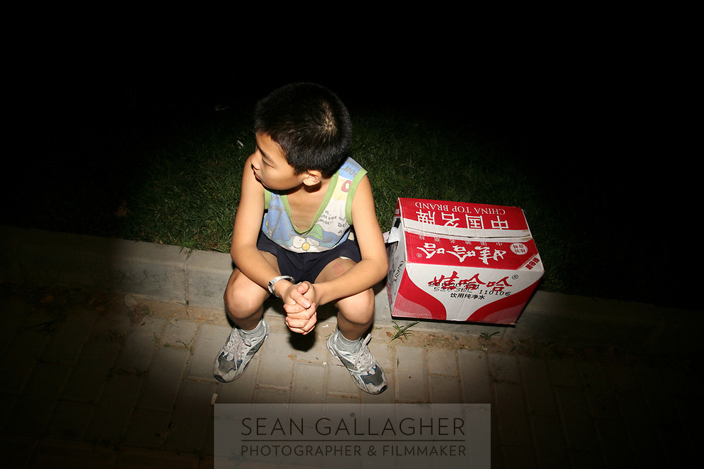 CHINA. Beijing. A young boy in the Olympic village whilst watching rehearsals for the Beijing Olympic games. 2008