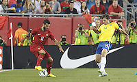 Portugal forward Vieirinha (11) dribbles as Brazil defender Maxwell (14) defends. In an international friendly, Brazil (yellow/blue) defeated Portugal (red), 3-1, at Gillette Stadium on September 10, 2013.