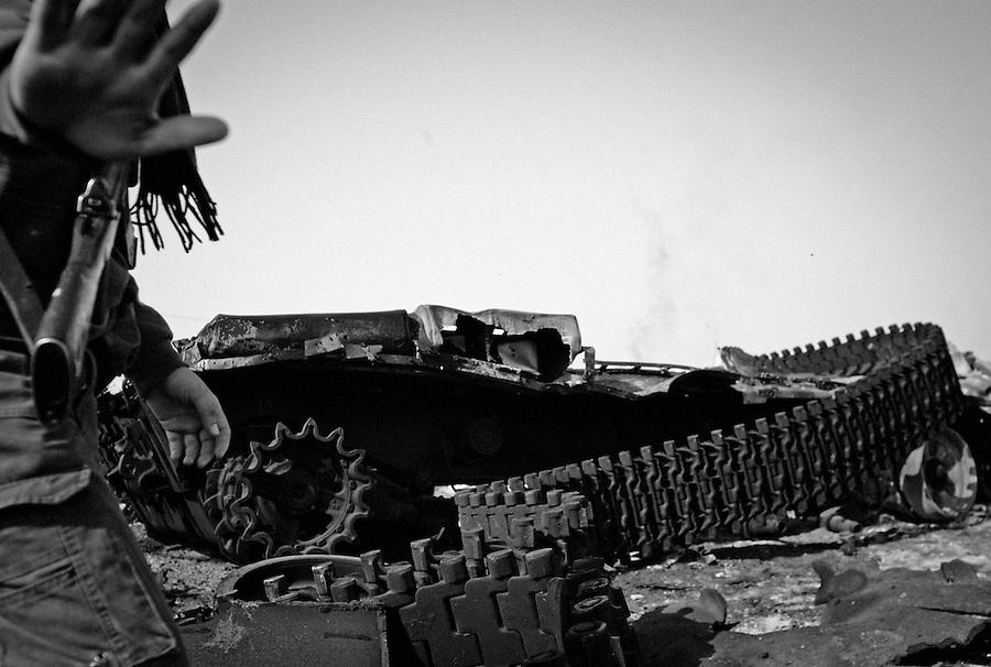 Rebel soldier walks infront of tank destroyed by NATO airstrike near the western gate of Ajdabiya, Libya.