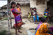 Young girls hold their siblings while women and their children meet for a weekly meeting to discuss health related issues in Bhelaiya village in Raxaul district in Bihar, India.