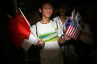 CHINA. Beijing. A young man selling flags from various nations in the shopping district of Wangfujing, a popular place for spectators, tourists and athletes to visit during the Olympic Games. 2008.