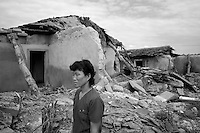 A woman stands near her destroyed home during a field visit by national and international Red Cross officials to Pongchon county, DPRK on Saturday August 27 2011. Consecutive floods caused by heavy rainfall and strong winds, together with the impact of typhoon Muifa which struck in early August, resulted in the destruction or severe damage of over 9,500 houses, rendering more than 25,000 people homeless between June 23 and August 9, according to data provided by the DPRK government. While flood damage was reported throughout the country, south and north Hwanghae provinces have been worst hit by the repeated flooding, leaving an already vulnerable population in a critical condition.  Photo by Morten Hvaal/Felix Features for IFRC.