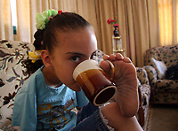 """Gaza.June.09.2008.Aya Masouad 8 years born without arms,use here toes and feet to go around with her daily life,sheshe drinking tea  , she love her life and thanking God, she practice her life as she is normal people . """" Photo by Thair Alhassany/propaimages"""""""