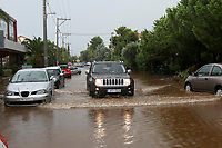 Pictured: A car wades through a flooded road in the Maroussi and Nea Erithrea areas of Athens, Greece. Thursday 26 July 2018<br /> Re: Torrential rain has affected areas of northern Athens, Greece.