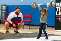 23 FEB 2014 - SMETHWICK, GBR - A young weightlifting fan, watched by his father, practices during a break at the 2014 English Weightlifting Championships at the Harry Mitchell Leisure Centre in Smethwick, Great Britain (PHOTO COPYRIGHT © 2014 NIGEL FARROW, ALL RIGHTS RESERVED)<br /> ==========================================<br /> USE WITH CARE - IMAGE FEATURES A CHILD UNDER  16 YEARS OLD<br /> ==========================================