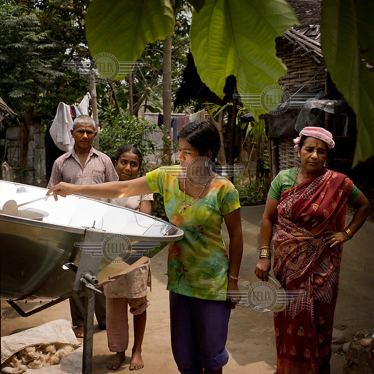 A family using a solar cooker at a Bhutanese refugee settlement. With the financial help of the Dutch Council for Refugees, a total of 6,300 solar cookers will be distributed amongst the Bhutanese refugees living in the region. The solar cookers consist of a reflective, aluminium, parabolic-shaped device that concentrates the sun's rays onto cooking pots placed on a frame in the centre of the dish. The dish has to be adjusted to the new position of the sun around every 10 minutes. It takes about 55 minutes to prepare a cooked meal on a sunny day and it is hoped that using the solar cookers will alleviate pressure on resources and reduce kerosene consumption by 75%...