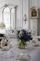 A pair of glass candelabra and a large vase of hyacinths and globe thistles are displayed on the dining room table