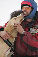 "Lance Mackey hugs his dog ""Scotch"" at the Rainy Pass checkpoint.  Monday, March 7.  2005 Iditarod Sled Dog Race"