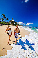 Surfer couple walking on the beach on a gorgeous day at Laniakea Beach on the North Shore of Oahu, Hawaii