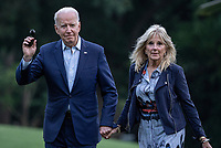United States President Joe Biden waves to the media as he and and first lady Jill Biden walk off of Marine One on the South Lawn of the White House in Washington, DC on Sunday, July 18, 2021. The Bidens spent the weekend at Camp David, the presidential retreat near Thurmont, Maryland.  <br /> CAP/MPI/RS<br /> ©RS/MPI/Capital Pictures