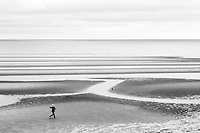 A man dances on the beach at lowtide in Eastham, MA.