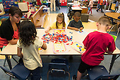 MR / Schenectady, NY. Zoller Elementary School (urban public school). Kindergarten inclusion classroom. Students work with pattern blocks at table with student teacher during math learning center time. MR: She4. ID: AM-gKw. © Ellen B. Senisi.