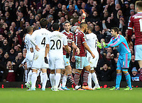 Sunday 07 December 2014<br /> Pictured: Swansea goalkeeper Lukasz Fabianski (R) is protesting for being shown a red card by referee Chris Foy (behind the players)<br /> Re: Premier League West Ham United v Swansea City FC at Boleyn Ground, London, UK.