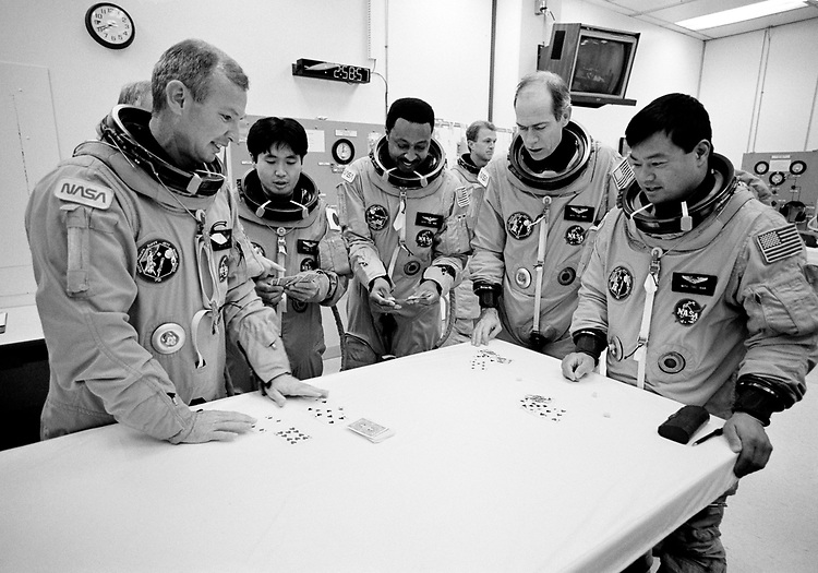 Image copyright John Angerson. <br /> STS-72 mission training.<br /> The crew play cards before the STS-72 simulated launch. Commander Brian Duffy, Pilot Brent W. Jett, Mission Specialists Leroy Chiao, Daniel T. Barry, Winston E. Scott, and Koichi Wakata.<br /> Kennedy Space Centre, Florida, USA.
