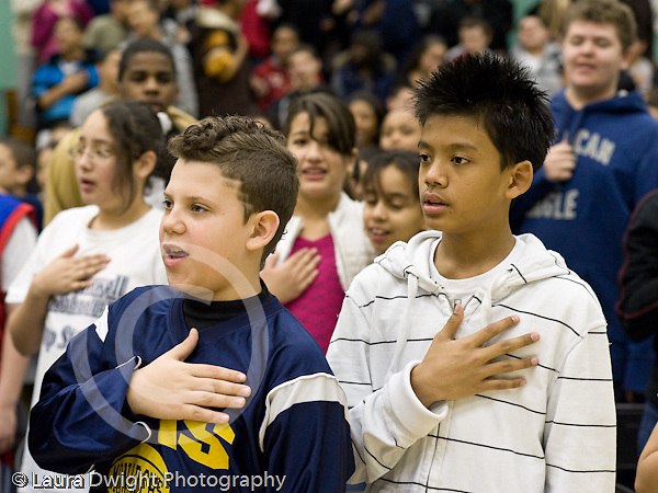Education Elementary school Grade 5 male students with hands on hearts saying the Pledge of Allegiance in gym with student body horizontal