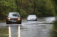 Pictured: A 4x4 drives past a Vauxhall Astra convertible which is stranded on the B4242 road between Resolven and Glyn Neath in south Wales, UK. Saturday 13 October 2018<br /> Re: Flooding caused by Storm Callum in the Neath area, south Wales, UK.