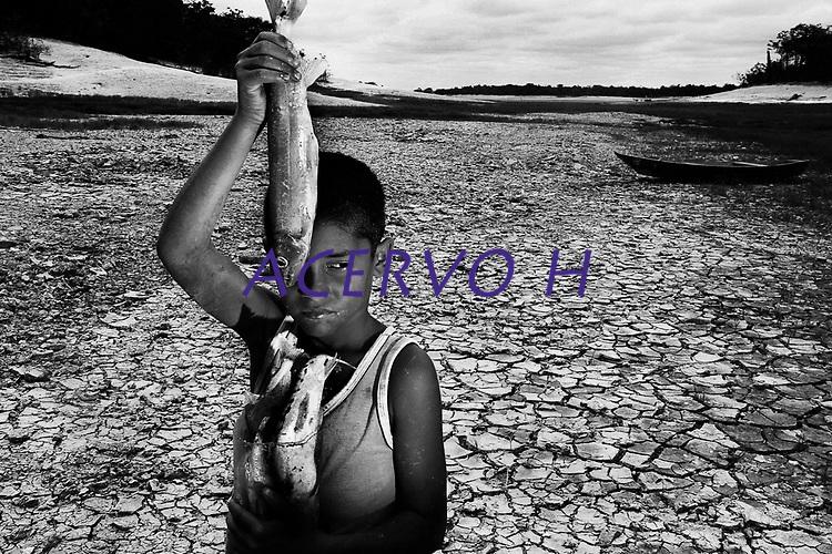 """Manaus- Amazonas 02 11 2010- SECA AMAZONAS. O garoto Ellias de Souza, 7 anos, mostra os  peixes que conseguiu pegar no igarapé do tarumã-mirim  na comunidade Nossa Senhora de Fátima, zona rural de Manaus. A série """" Seca no Amazonas"""", documenta  a maior seca já registrada no  estado desde que  o nível dos rio Amazonas e rio Negro passaram a ser monitorados em 1905. Eventos extremos estão se tornando cada vez mais comuns para a população que tenta adaptar-se a a cada período de estiagem na região. (Foto Alberto Cesar Araujo)"""