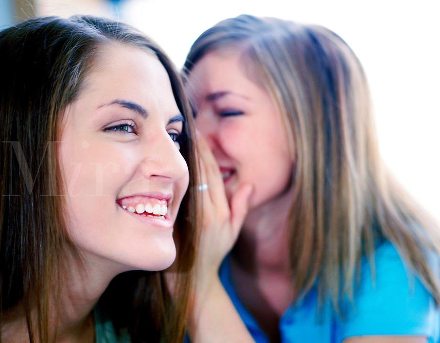 2 teenage girls telling secrets, smiling and laughing.