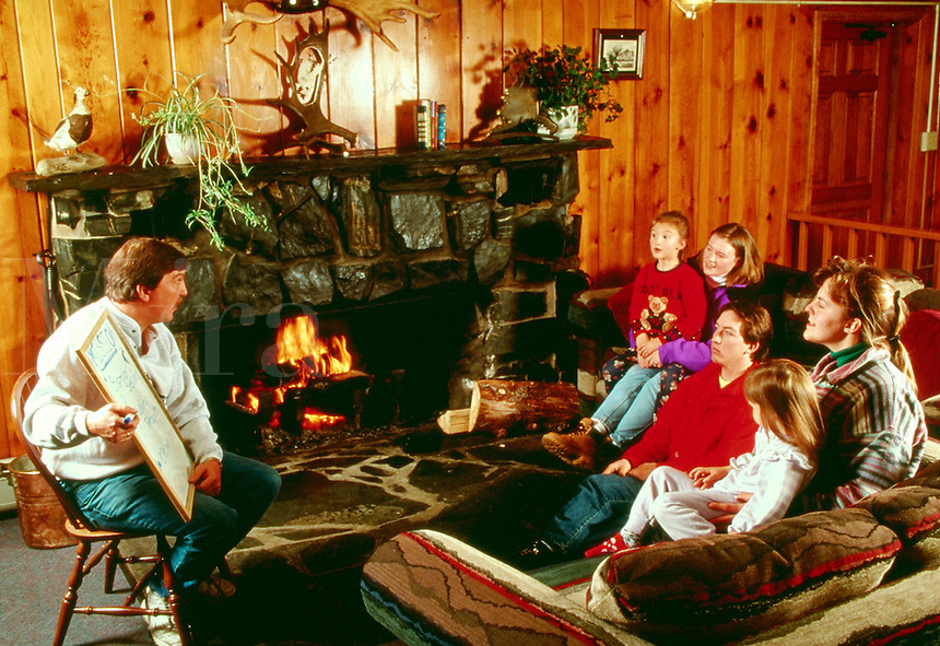 Group of people meet in a lodge to listen to a seminar, meeting, discussion, group interaction. Parents and kids at lodge.