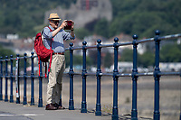 WEATHER PICTURE WALES<br /> Pictured: A man takes a photo on his phone down the seafront in Mumbles, near Swansea, Wales, UK. Thursday 22 July 2021<br /> Re: High temperatures and sunshine has been forecast for most of the UK.