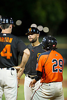 AZL Giants manager Hector Borg (13) talks to coach Bill Horton (14) after a hard tag applied to Ismael Munguia (29) at first base during the game against the AZL Reds on August 12, 2017 at Scottsdale Stadium in Scottsdale, Arizona. AZL Giants defeated the AZL Reds 1-0. (Zachary Lucy/Four Seam Images)
