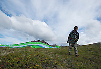 A paraglider prepares to launch from a ridge line above Eagle River, Alaska.