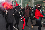 """© Joel Goodman - 07973 332324 . 26/03/2011 . London , UK . A black bloc of protesters carrying black and red anarcho-syndiclist flags in Piccadilly Circus . Hundreds of thousands of people attending an anti cuts demonstration under the banner """" March for the Alternative """" in central London , in protest at the coalition government's austerity measures . Photo credit : Joel Goodman"""