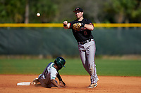 Omaha Mavericks shortstop Keil Krumwiede (11) throws to first base as Blake Crossing (13) slides into second during a game against the Dartmouth Big Green on February 23, 2020 at North Charlotte Regional Park in Port Charlotte, Florida.  Dartmouth defeated Omaha 8-1.  (Mike Janes/Four Seam Images)