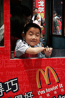 A child hangs out of a tourist trolley window with McDonald's advertisement in Shanghai, China.
