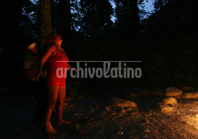 """Under the command of a santeria pristess (in red) 21-year-old Andrea Gómez lies in a ¨healing gate"""" to   heal her psychological pregnancyy  in the Sorte Mountains in Yaracuy State, the center of popular religions in Venezuela. Picture is part of an  essay by Howard Yanes The Borders of Faith in Venezuela. Howard says :""""This are religions or beliefs from which no one speaks clearly but everydoby  knows they exist. Everybody pretends they are irrelevant, some of them even could laugh about this beliefs  but nobody would dare to remove those pieces of voodoo ceremony you can find at any cementery, or to close down the illegal shops selling animals for sacrifice."""""""