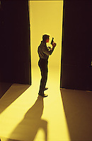 Man with gun on yellow seamless walking away from camera<br />
