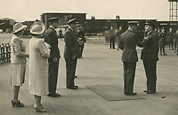 BNPS.co.uk (01202) 558833. <br /> Pic: Spink&Son/BNPS<br /> <br /> Pictured: Wing Commander Sidney 'Tubby' Baker receiving his DSO from King George VI with a young Princess Elizabeth and the Queen looking on in 1944.<br /> <br /> The bravery medals of a larger-than-life hero Pathfinder pilot who clocked up a staggering 100 bombing raids have emerged for sale for £32,000.<br /> <br /> Wing Commander Sidney 'Tubby' Baker, who was known for his love of food, drink and cigarettes, repeatedly risked his life in attacks on heavily defended German and Italian targets.<br /> <br /> Upon returning to his airbase after completing his century, the No 635 Squadron commander was handed a well-earned pint of beer and 'grounded with immediate effect'.<br /> <br /> As was his custom, he downed the drink and puffed on a celebratory cigarette.