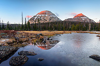The first sun rays of a chilly October morning warm the 11,500 foot  summits of Bald Mountain and Reids Peak while open water gives way to encroaching ice on Pass Lake.  Uinta Mountains, Utah.