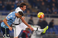 Calcio, Serie A: Lazio vs Juventus. Roma, stadio Olimpico, 4 dicembre 2015.<br /> Lazio's Mauricio, left, and Juventus' Mario Mandzukic jump for the ball during the Italian Serie A football match between Lazio and Juventus at Rome's Olympic stadium, 4 December 2015.<br /> UPDATE IMAGES PRESS/Riccardo De Luca
