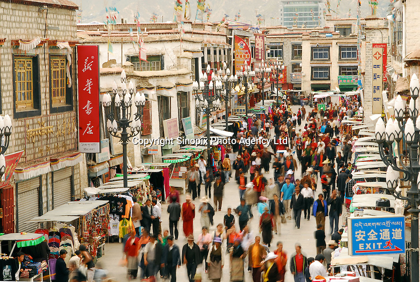 Tibetans in the market streets of Central Lhasa, mingle with tourists,Tibet, China. Lhasa is becomming swamped by tourists, especially Chinese, with the recently opened Golmud to Lhasa train and more and more flights arriving on a daily basis..