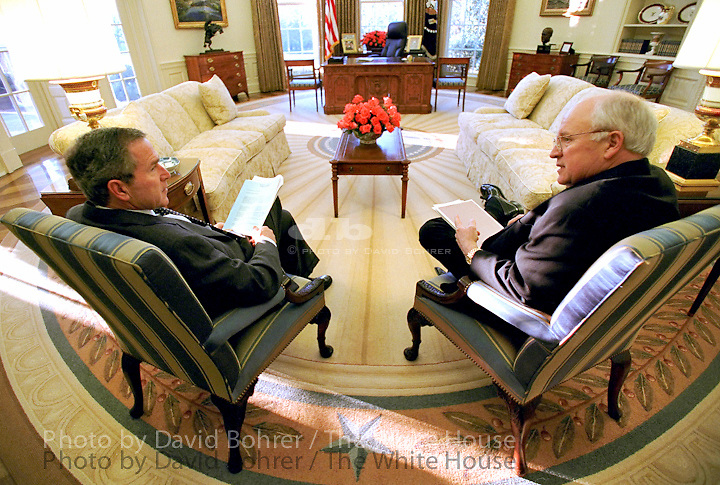 """President George W. Bush Vice President Dick Cheney talk together before their morning intelligence briefing, March 1, 2002, in the Oval Office. Printed in the Marine Corps University Foundation Program/ slide show  Released to: Grizzly Adams Productions 5.4.04    Released to: Randomhouse Publishing 6.22.07 Used for Photos of Note March 1 - 9, 2002.   PON Used in OVP  2002 Christmas Slide Show  WEB  WEST WING JUMBO  WEB. CROP. COLOR CORRECT..Released to Video Art Productions for the National Portrait Gallery exhibition, """"Presidents in Waiting."""".2008 Christmas Slideshow"""