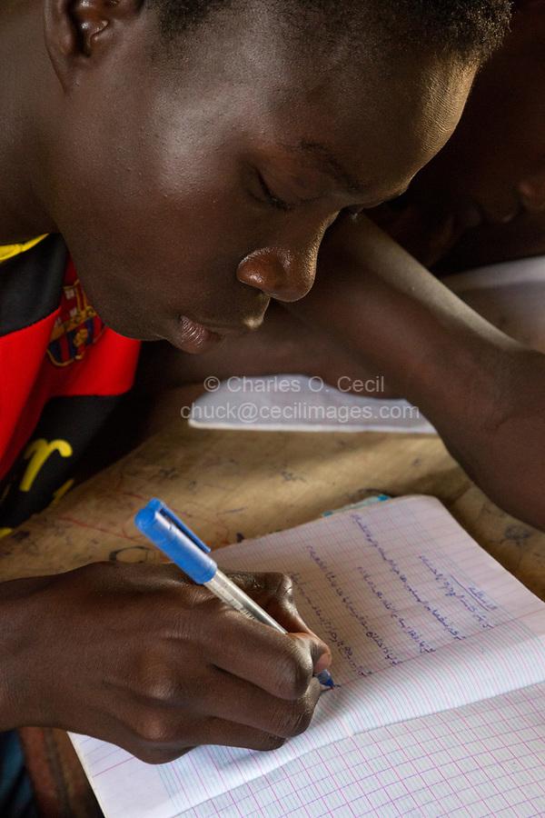 Senegal, Touba.  Boy  at Al-Azhar Madrasa, a School for Islamic Studies, writing in Arabic in his notebook.