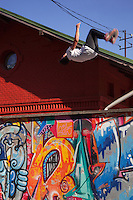 Romania. Iași County. Iași. A teenage boy performs during a parkour a backflip on a wall covered with colorful graffitis. The backflip is an act of rotating one's body 360 degrees in the backward direction. Parkour is a training discipline using movement that developed from military obstacle course training. Practitioners aim to get from A to B in the most efficient way possible. This is done using only the human body and the surroundings for propulsion, with a focus on maintaining as much momentum as possible while still remaining safe. Parkour can include obstacle courses, running, climbing, swinging, mantling, vaulting, jumping, rolling, quadrupedal movement, and other, similar movements depending on what movement is deemed most suitable for the given situation. Parkour's development from military training gives it some aspects of a non-combative martial art. Iași (also referred to as Iasi, Jassy or Iassy) is the largest city in eastern Romania and the seat of Iași County. Located in the Moldavia region, Iași has traditionally been one of the leading centres of Romanian social life. The city was the capital of the Principality of Moldavia from 1564 to 1859, then of the United Principalities from 1859 to 1862, and the capital of Romania from 1916 to 1918. 12.06.15© 2015 Didier Ruef